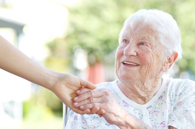 A elderly woman shaking hands with a career